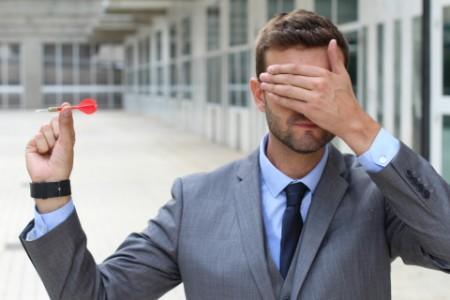 бизнесмен с закрытыми глазами держит дротик