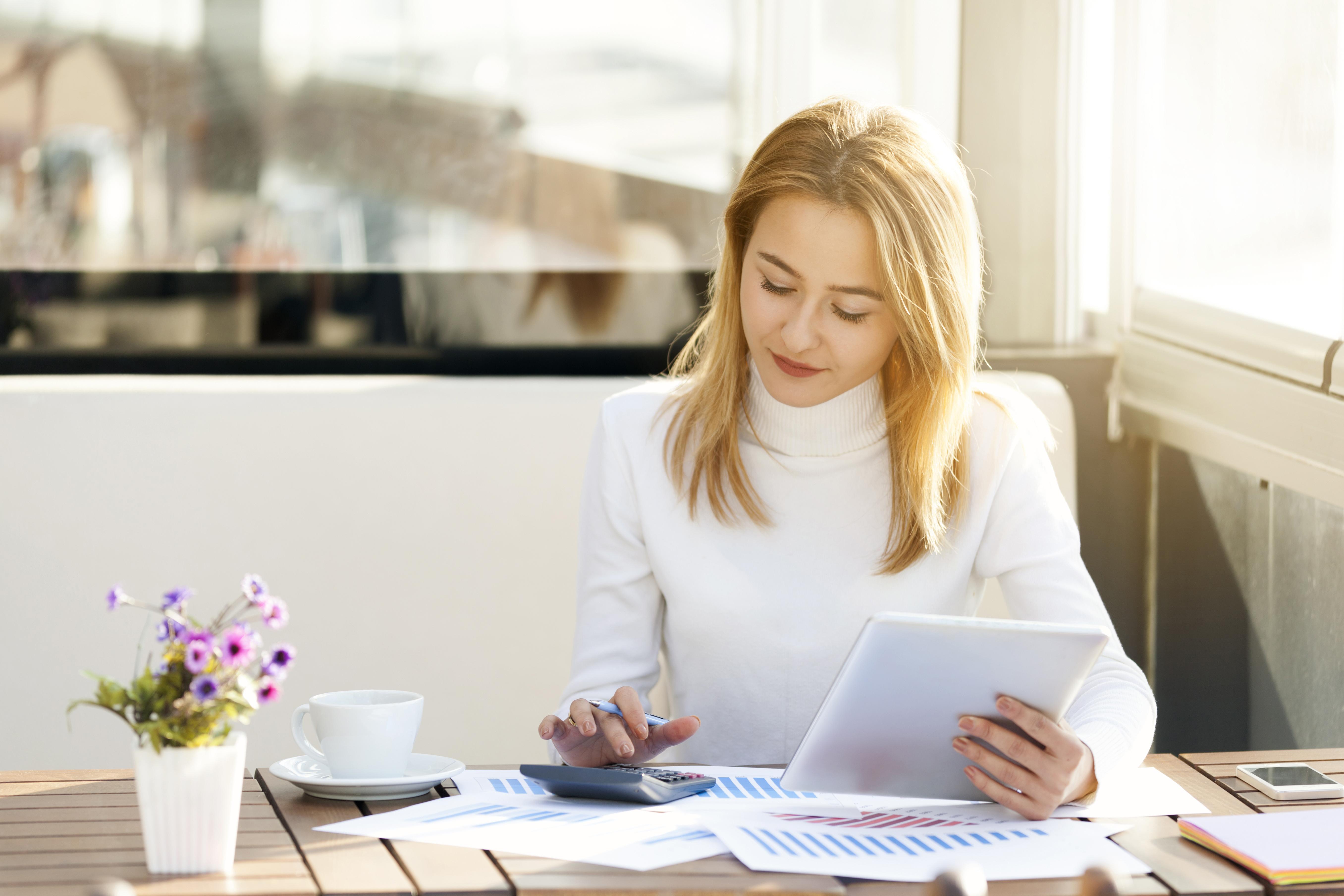 Ženska zamišljeno gleda tablični računalnik