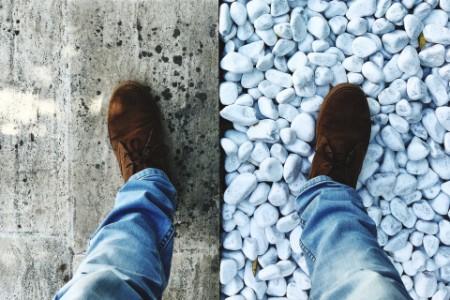 Moški stoji na dveh različinih podlagah