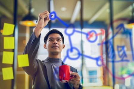 Businessman Holding Coffee Mug and Writing Data on Transparent Board