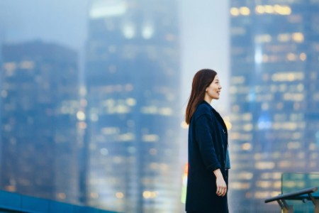 Confident Businesswoman with Smile Standing Against Illuminated Urban City Skyline at Dusk