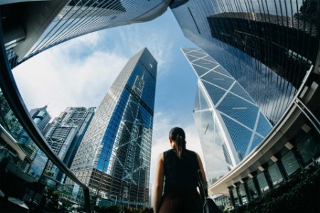 Rear view of businesswoman standing against contemporary financial skyscrapers in Hong Kong