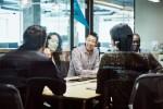 商人在会议室微笑着跟客户见面